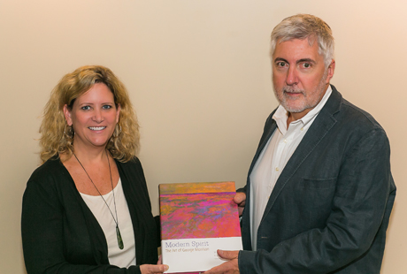 Jennifer Jones and David Fraher holding the exhibition catalog.