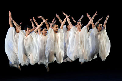Dancers in flowing, white costumes leaping in the air
