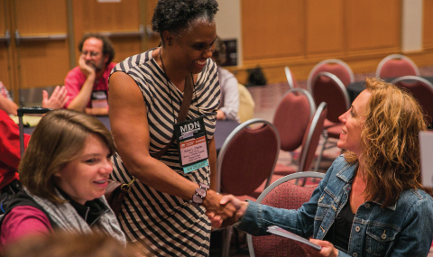 Two conference attendees shaking hands.