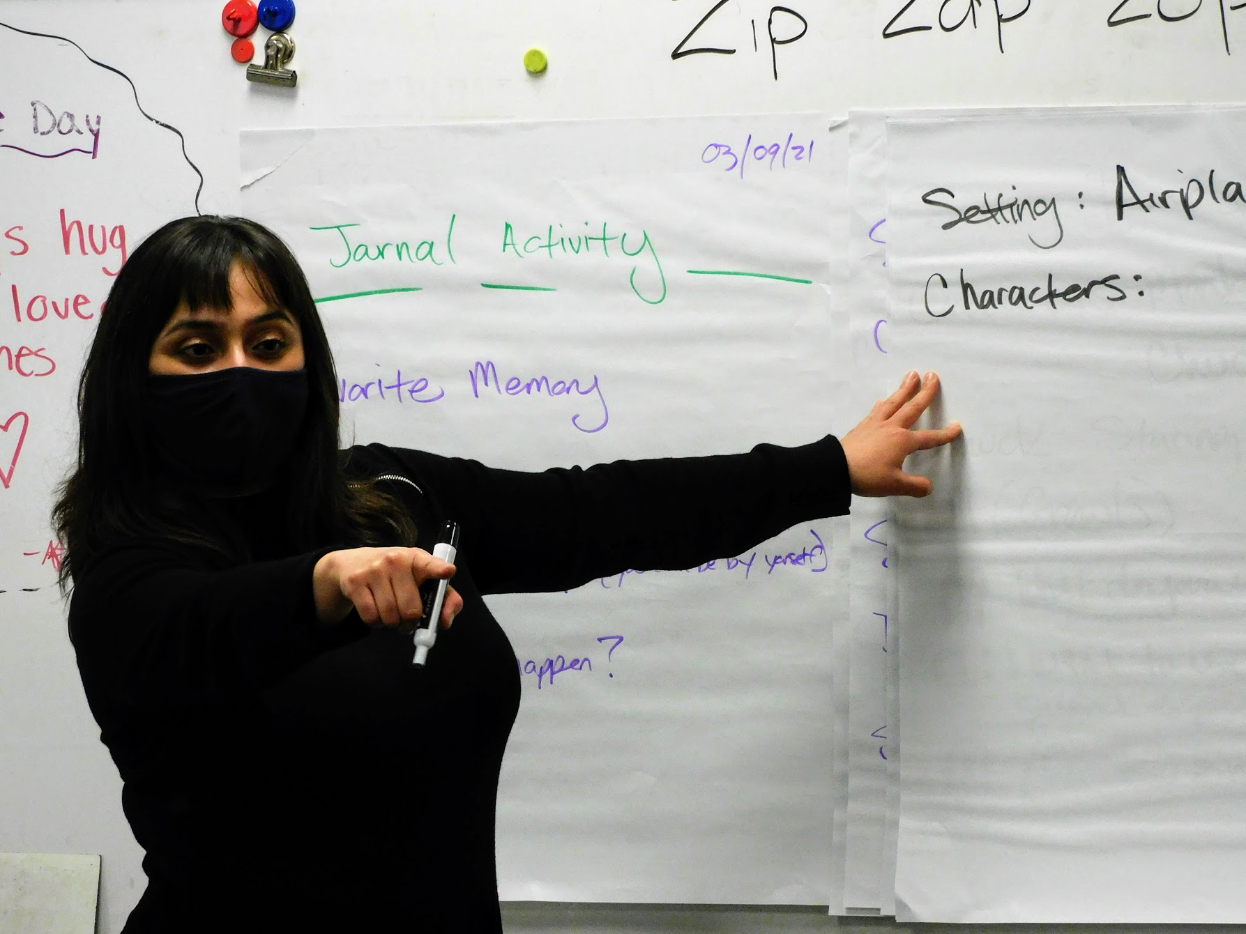 A woman in a black mask and sweater stands in front of writing on a board.