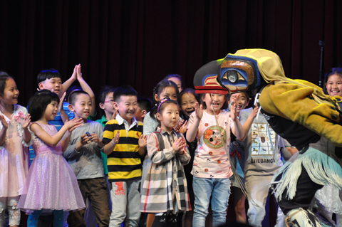 Young children on stage with a large bird puppet