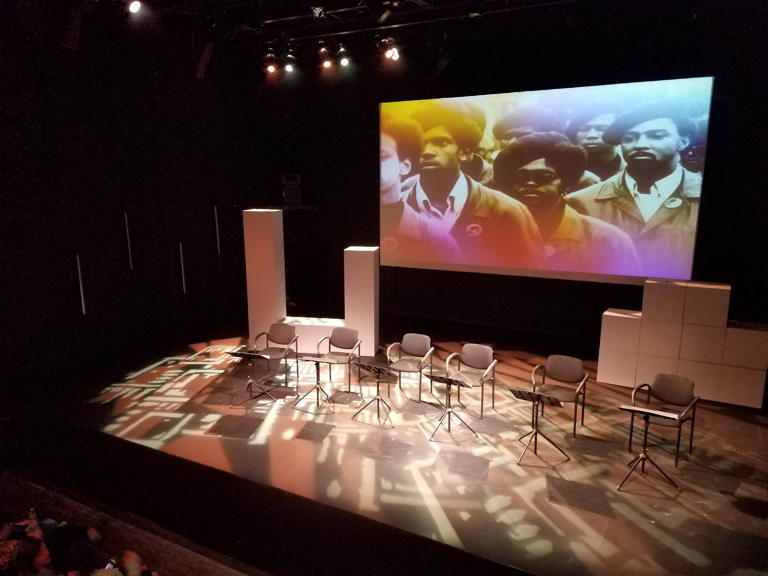 Stage with empty chairs and projected backdrop