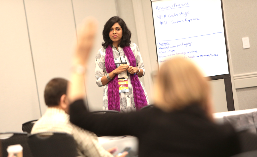 Patel leads a session as a participant raises her hand
