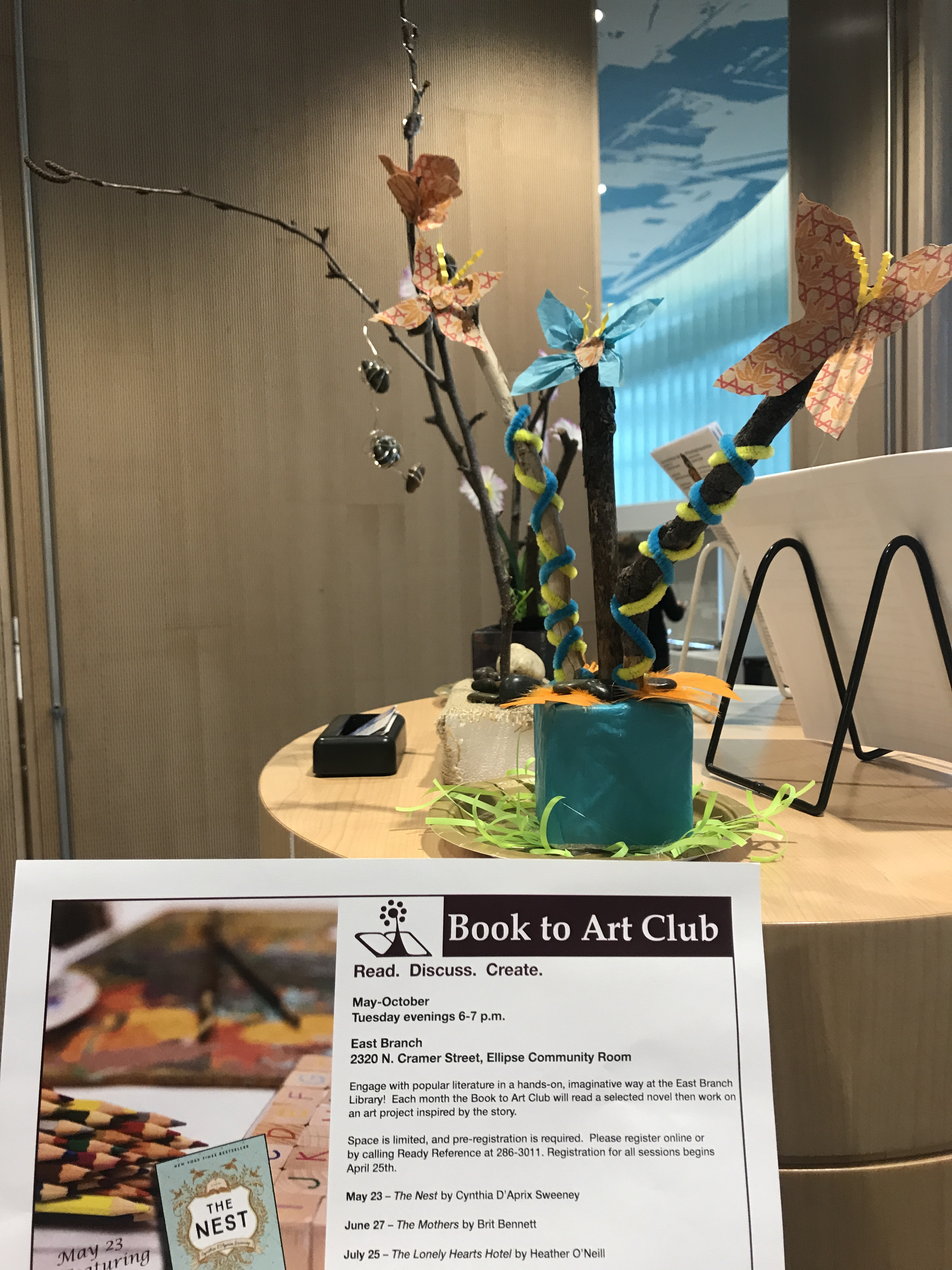 Book discussion sign with butterfly art in background