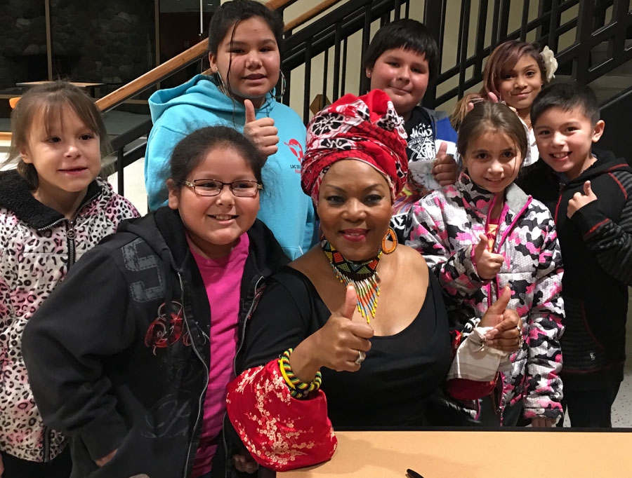 Lorraine Klaasen gives the thumbs up posing with seven students who attended her public concert