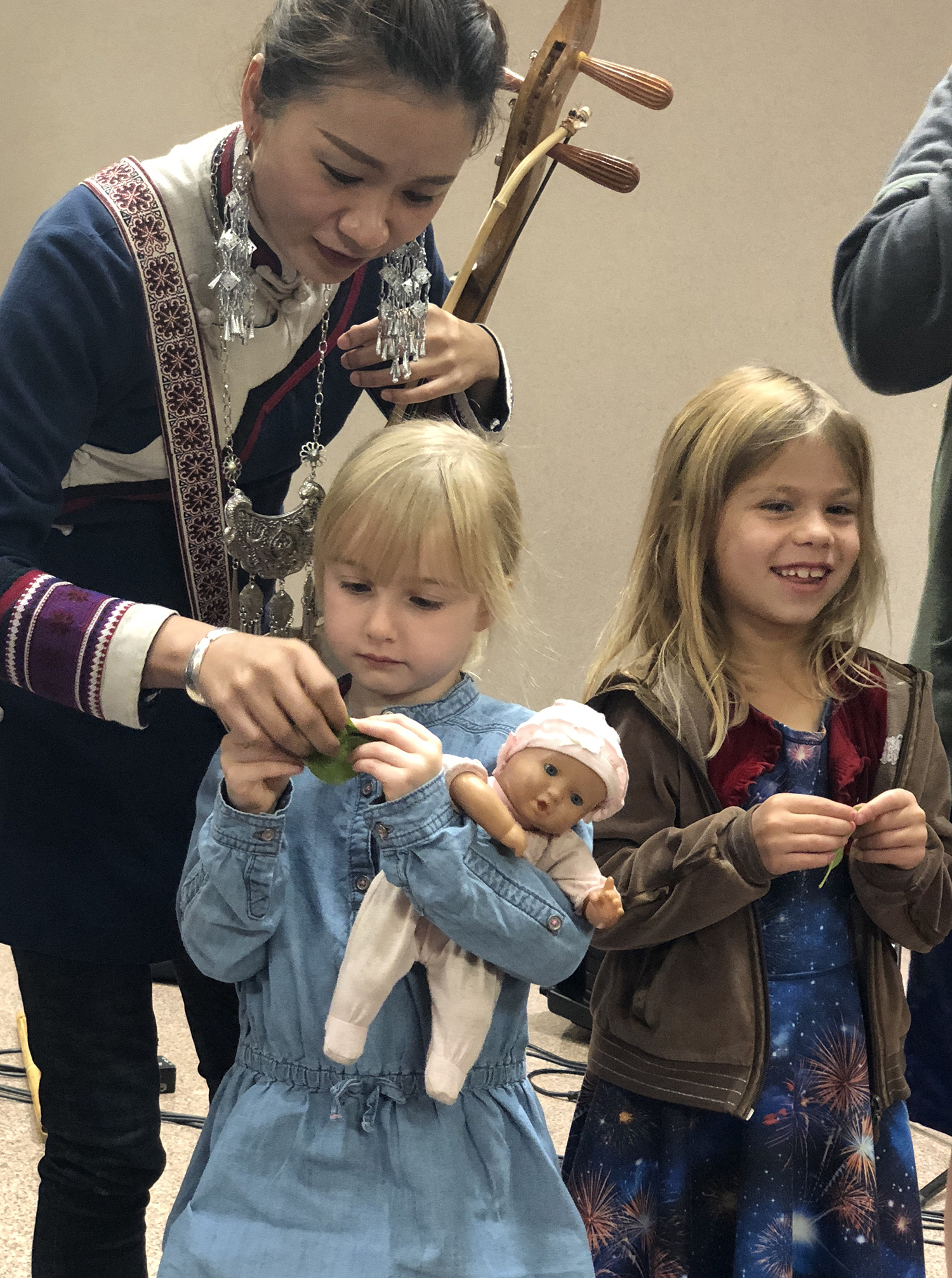 Home school children came to attend the workshop. 4 year old girl with her doll in her arm tried to play the leaf. Alan gently showed her how to hold the leaf.