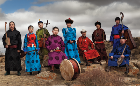 nine musicians post with traditional Mongolian instruments and dress with landscape background