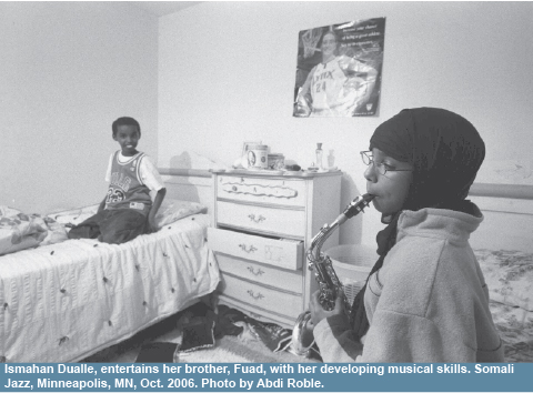 Roble's photograph from the Somali Documentary Project: Ismahan Dualle, entertains her brother, Fuad, with her developing musical skills. Somali Jazz, Minneapolis, MN, Oct. 2006.