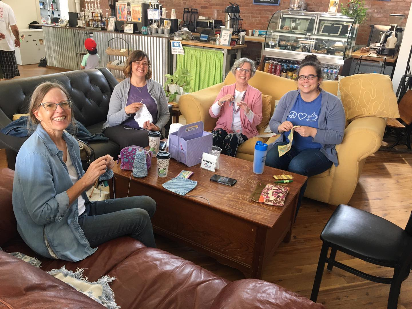 Four women holding knitting materials sit around a table.