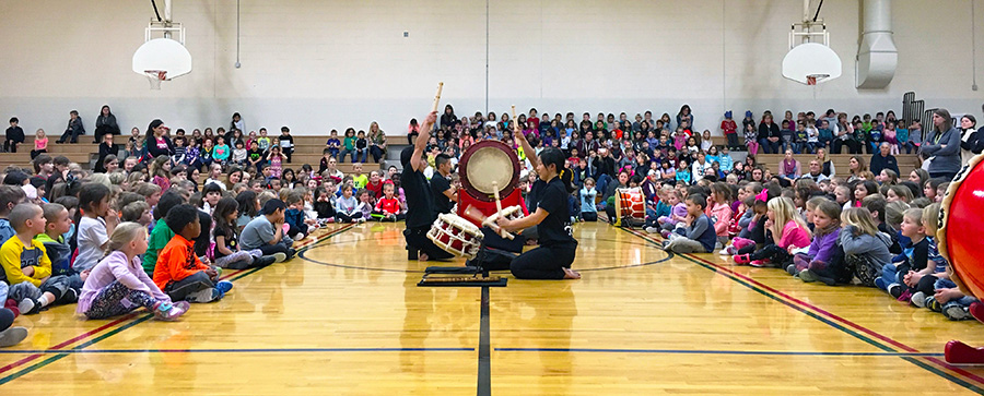Large taiko drum in the center of an elementary school gymnasium with kids all around to watch the performance