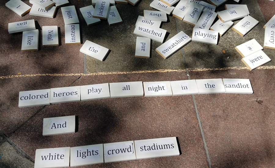 Sidewalk poem reads: colored heroes play all night in the sandlot / And / white lights crowd stadiums