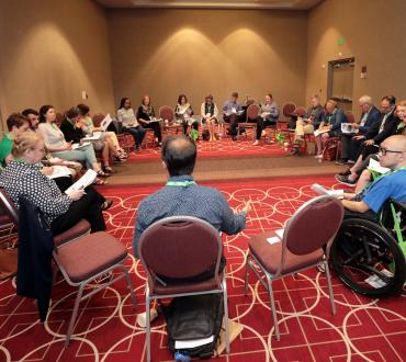 A group of attendees sit in a circle at a professional development session for the 2019 Arts Midwest Conference.