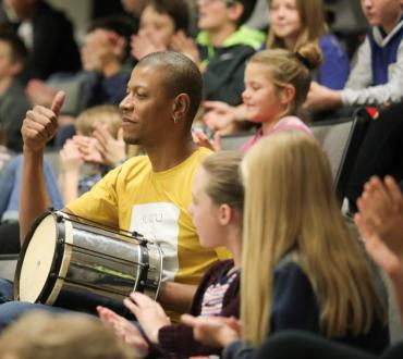 Man with drum surrounded by students
