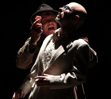 Two men perform on stage in dark light