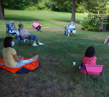Women sit outside socially distanced at a book club event