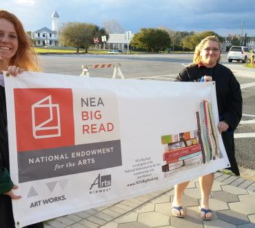 two students in graduation robes holding an NEA Big Read banner