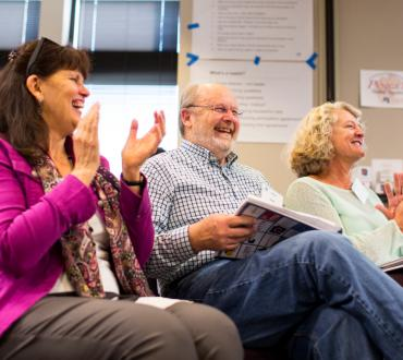 Photo of three people, smiling and clapping at an ArtsLab retreat
