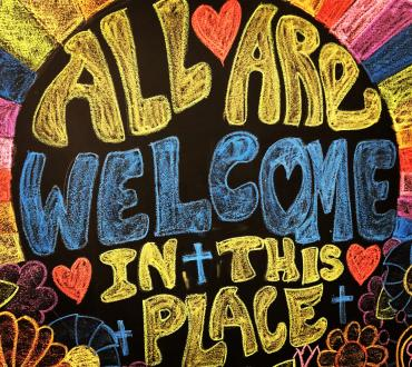 """Chalkboard with """"All Are Welcome In This Place"""" written in yellow and blue lettering"""
