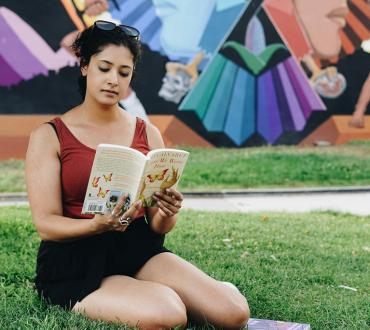 A young woman sits in the grass reading In the Time of the Butterflies by Julia Alvarez