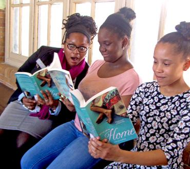 Three girls read books together