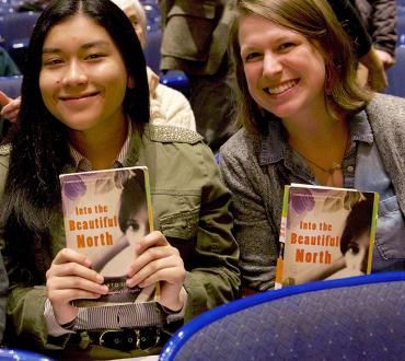 Students hold up their copies of the book Into the Beautiful North at a Big Read event