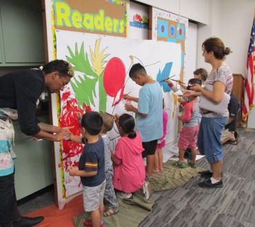 Six children gathered at a mural, painting, as two teachers assist