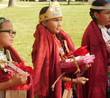 Young red shawl dancers holding books