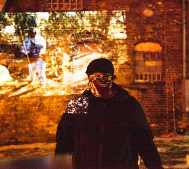 Man with a masks stands in front of projection on brick wall