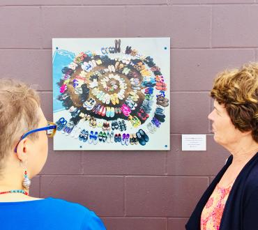 Two woman look at an art print hung on a wall of multicolored shoes arranged in a circle