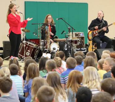 Unni Boksasp Ensemble at St. Joseph's School in Pierre with students filling the gym floor. Photo by Eric Young Smith.