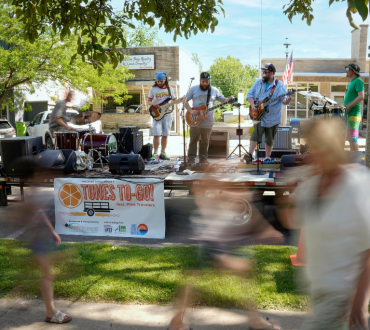 Blurred people pass by a band playing on stage