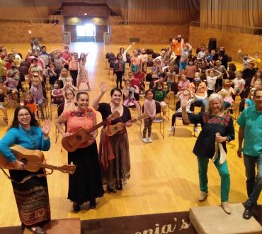 A group of five people holding instruments stands in front of a crowd of children at an indoor performance venue.