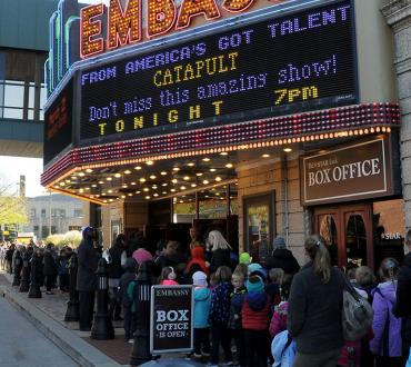 A photo of a brightly-lit theater marquee with a line of people outside.