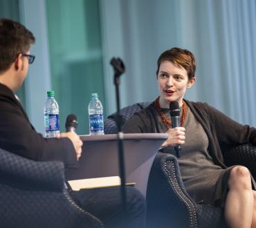 Author Emily St. John Mandel speaking into a microphone, in conversation with a UCF professor