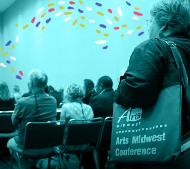 Blue image of conference attendee entering a room with sparkles overlaid