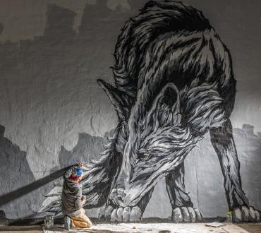 Man paints a large mural of a fox