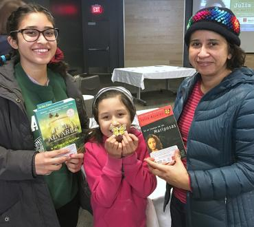 Participants posing with book and crafts made during a NEA Big Read event.
