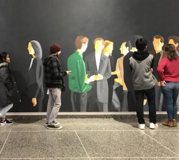 Four young people stand in front of a wall painted with a mural of people connecting and talking
