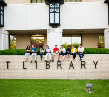 "Seven people reading while sitting on a stone wall that says ""Library"""