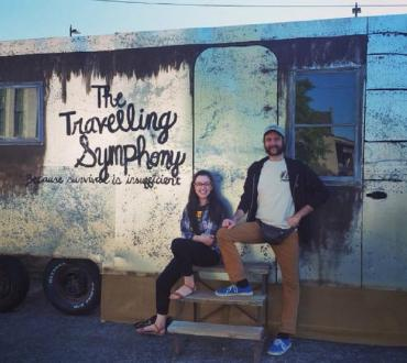 "Two people standing in front of a bus that says ""The Traveling Symphony"""