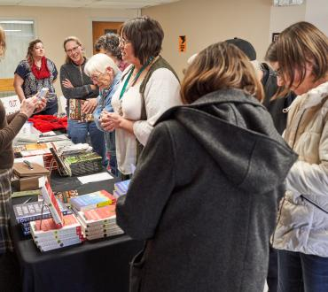 crowd gathered around table of books