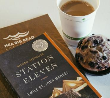 book sitting on a pamphlet next to a muffin and a cup of coffee
