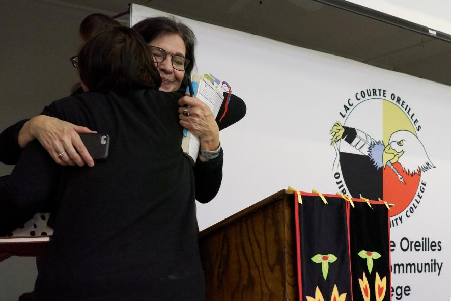 woman in glasses hugging other person behind podium